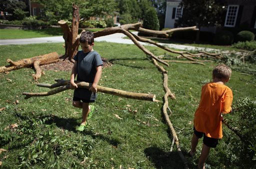 Cormac Worrall, 6, left, helps his father remove tree debris from their yard in Virginia Beach, Va, on Sunday, Sept. 4, 2016. (Vicki Cronis-Nohe /The Virginian-Pilot via AP)