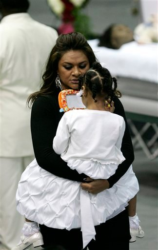 Loleini Tonga, fiancee of Cincinnati Bengals wide receiver Chris Henry, holds their daugther, Seini, before a memorial service for Henry in Westwego, La., Tuesday, Dec. 22, 2009. (AP Photo/Patrick Semansky)