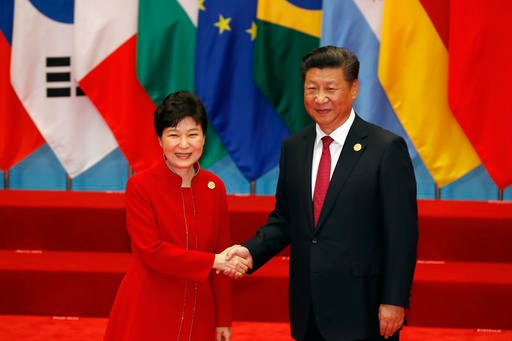 South Korean President Park Geun-hye, left, shakes hands with China's President Xi Jinping before a group photo session for the G-20 Summit in Hangzhou in eastern China's Zhejiang province, Sunday, Sept. 4, 2016. (AP Photo/Ng Han Guan)