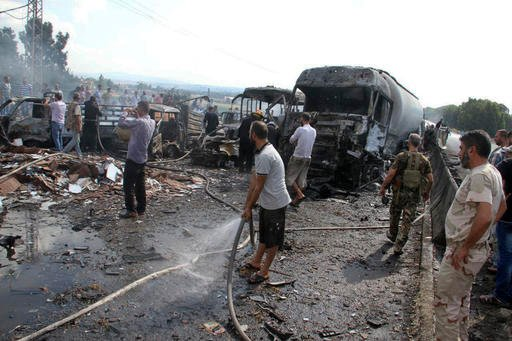 In this photo released by the Syrian official news agency SANA, Syrian security forces, emergency services and residents look at the remains of burned vehicles at the site of a bombing in Tartus, Syria, Monday, Sept. 5, 2016. Syrian state media reported t