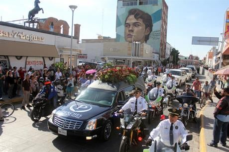 Juan Gabriel, a superstar and an icon in the Latin music world, died on Aug. 28 at his home in California at age 66. A mural of him covers a building in the background. (AP Photo/Raymundo Ruiz)