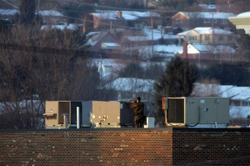 A police sniper observes from a rooftop vantage point the Wytheville Post Office on Main Street in Wytheville, Va., Wed, Dec. 23, 2009. An armed man took hostages at a post office in a rural town, officials said. (AP Photo/The Roanoke Times, Matt Gentry)