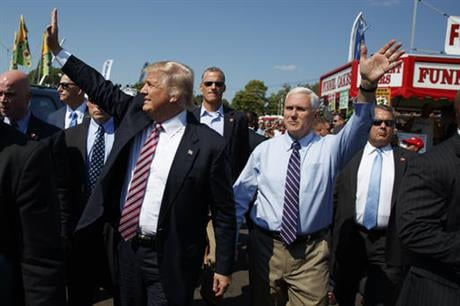 Republican presidential candidate Donald Trump, center left, waves as he walks with vice presidential candidate Gov. Mike Pence, R-Ind., center right, during a visit to the Canfield Fair, Monday, Sept. 5, 2016, in Canfield, Ohio. (AP Photo/Evan Vucci)