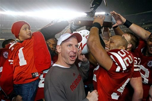 Nebraska coach Bo Pelini, center, hoists the trophy with his team after Nebraska defeated Arizona 33-0 in the Holiday Bowl NCAA college football game Wednesday, Dec. 30, 2009, in San Diego. (AP Photo/Chris Park)
