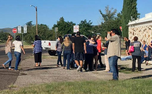 People gather near the Alpine High School campus after a shooting, in Alpine, Texas.