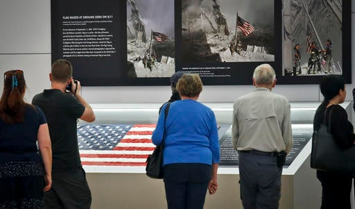 Visitors view the display for the American flag, left, that firefighters hoisted at ground zero in the hours after the 9/11 terror attacks, Thursday Sept. 8, 2016, at the Sept. 11 museum in New York. After disappearing for more than a decade the 3-foot-by