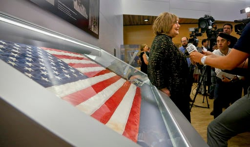 Shirley Dreifus, center, the original owner of the American flag, left, that firefighters hoisted at ground zero in the hours after the 9/11 terror attacks, hold interviews at the Sept. 11 museum, Thursday Sept. 8, 2016, in New York. After disappearing fo