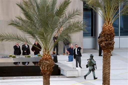Workers wait with law enforcement at the Lloyd D. George federal courthouse building in downtown Las Vegas following a shooting, Jan. 4, 2010. A court officer and the suspect were killed, a second officer is in serious condition. (AP Photo/Isaac Brekken)