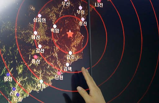 An official of the Earthquake and Volcano of the Korea Monitoring Division points at the epicenter of seismic waves in North Korea, in Seoul, South Korea.