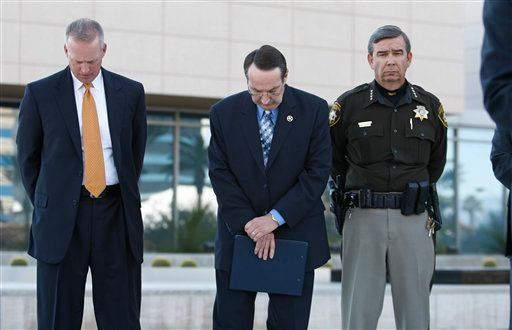 FBI Special Agent Joseph Dickey, left, and U.S. Marshall Gary Orton, center, bow their heads as Las Vegas Sheriff Douglas Gillespie, right, listens during a news conference at the federal building in Las Vegas, Tuesday, Jan. 5, 2010. AP Photo/Paul Sakuma