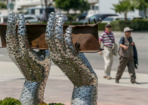 "Pedestrians walk by artist Heath Satow's sculpture ""Reflect,"" made with a damaged, rusted I-beam."