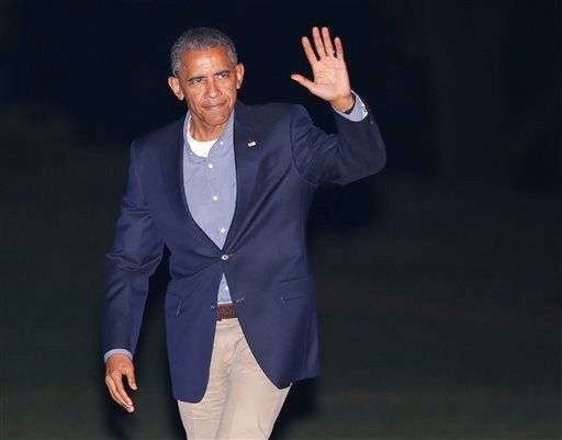 President Barack Obama waves to members of the media as he walks across the South Lawn of the White House in Washington.