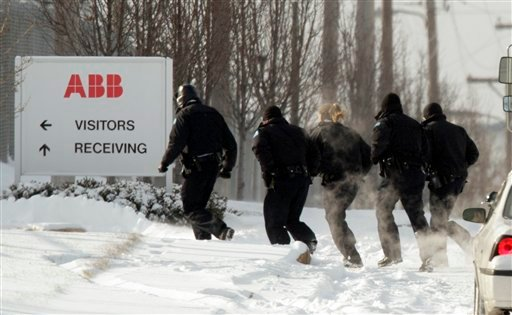 Police run into a building as they search for a gunman who walked into the ABB Power plant with an assault rifle and began shooting Thursday, Jan. 7, 2010, in St. Louis. (AP Photo/Jeff Roberson)