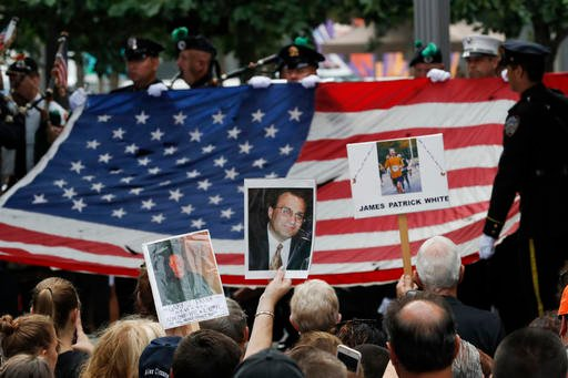 Mourners hold photos of their loved ones during the 15th anniversary of the attacks of the World Trade Center at the National September 11 Memorial, Sunday, Sept. 11, 2016, in New York. (AP Photo/Mary Altaffer)