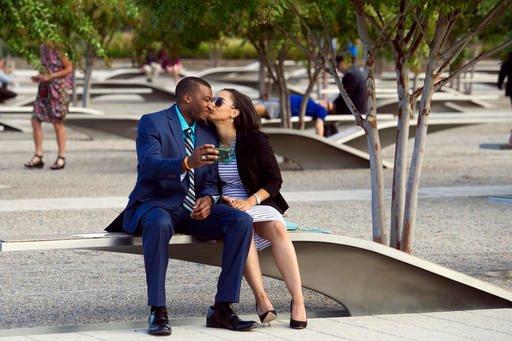 A couple kisses while visiting the Pentagon Memorial prior to a Sept. 11 observance ceremony at the Pentagon, Sunday, Sept. 11, 2016. (AP Photo/Cliff Owen)