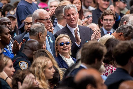 Democratic presidential candidate Hillary Clinton, center, accompanied by Sen. Chuck Schumer, D-N.Y., center left, Rep. Joseph Crowley, D-N.Y., second from left, and New York Mayor Bill de Blasio, center top, attends a ceremony at the Sept. 11 memorial, i