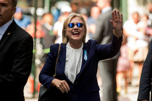 Democratic presidential candidate Hillary Clinton waves after leaving an apartment building Sunday, Sept. 11, 2016, in New York. Clinton's campaign said the Democratic presidential nominee left the 9/11 anniversary ceremony in New York early after feeling