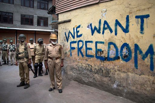 In this Aug. 12, 2016, file photo, Indian policemen stand guard during a curfew in Srinagar, Indian-controlled Kashmir. As Kashmir enters a third month of tense conflict marked by violent street clashes and almost daily protests following the July 8, 201