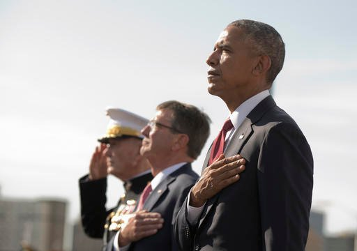 President Barack Obama, right, with Defense Secretary Ash Carter, center, and Chairman of the Joint Chiefs of Staff Gen. Joseph Dunford, stand at attention as the national anthem is played during a memorial ceremony at the Pentagon in Washington, Sunday,