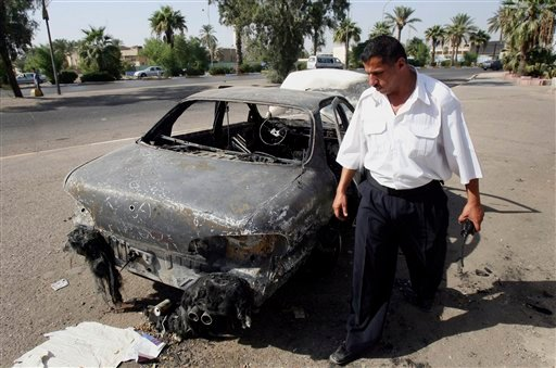 FILE - In this Thursday, Sept. 25, 2007 file photo, an Iraqi traffic policeman inspects a car destroyed by a Blackwater security detail in al-Nisoor Square in Baghdad, Iraq.