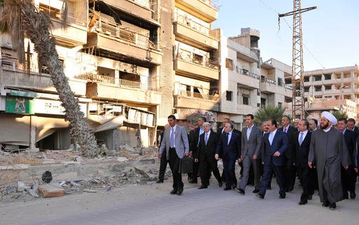 In this photo released by the Syrian official news agency SANA, Syrian President Bashar Assad, center, walks on a street with officials after performing the morning Eid al-Adha prayers in Daraya, a blockaded Damascus suburb, Syria, Monday, Sept. 12, 2016.