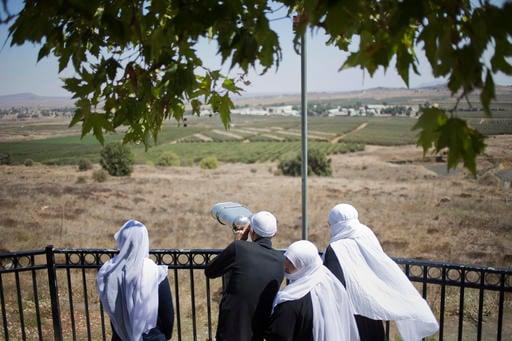 A Druze family, celebrating the Eid al-Adha holiday, look towards Syria's Quneitra province.