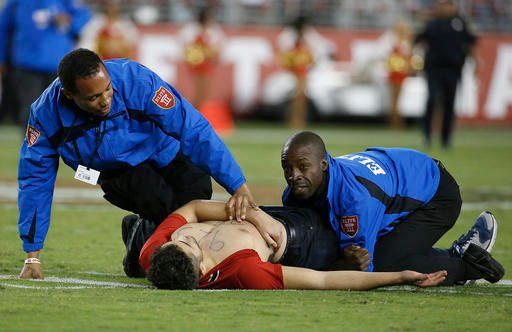 In this Sept. 12, 2016, file photo, a fan is tackled by security officers during the second half of an NFL football game between the San Francisco 49ers and the Los Angeles Rams in Santa Clara, Calif.