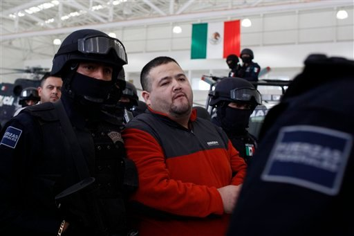 """eodoro Garcia Simental, known as """"El Teo,"""" center, is escorted by federal police after being presented to the press in Mexico City, Tuesday, Jan. 12, 2010. (AP Photo/Alexandre Meneghini)"""