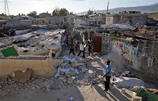 People walk among debris in Port-au-Prince, Thursday, Jan. 14, 2010. A powerful earthquake struck Haiti Tuesday. (AP Photo/Gregory Bull)