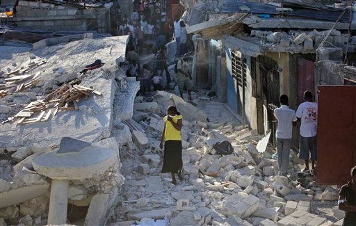 A woman walks among debris in Port-au-Prince, Thursday, Jan. 14, 2010. A 7.0-magnitude earthquake struck Haiti Tuesday. (AP Photo/Gregory Bull)