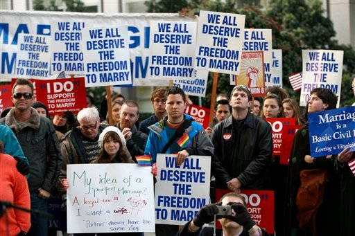 Supporters of same-sex marriage huddle outside of the federal courthouse in San Francisco, Monday, Jan. 11, 2010. (AP Photo/Marcio Jose Sanchez)