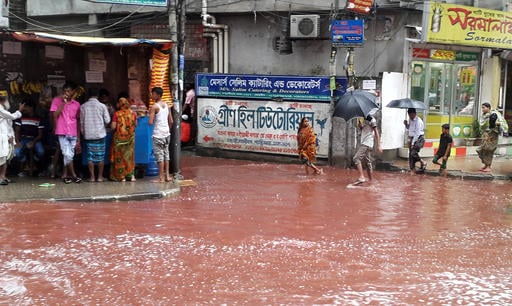 In this Tuesday, Sept. 13, 2016 photo, people wade past a road turned red after blood from sacrificial animals on Eid al-Adha mixed with water from heavy rainfall in Dhaka, Bangladesh. Authorities in Dhaka had assigned several places in the city where res