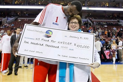 Haiti native Samuel Dalembert, left, of the Philadelphia 76ers, hugs Caryl Stern, president and CEO of the U.S. Fund for UNICEF, as he presents her with a check for $100,000 to aid relief efforts in Haiti.