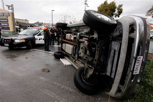 Huntington Beach Police officers stand by a vehicle that flipped over in high winds during a tornado warning Tuesday Jan. 19, 2010 in Huntington Beach, Calif.