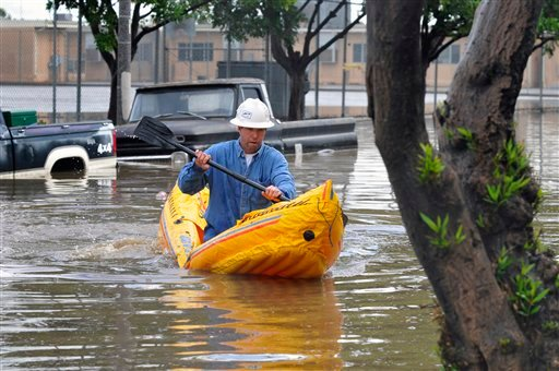 Jerry Bridges paddles an inflatable kayak down a flooded section of Bennett Aveue in Long Beach, Calif., Tuesday, Jan. 19, 2010. (AP Photo/Scott Smeltzer)