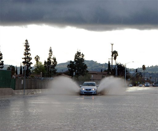 A car drives through a flooded street in the Sun Valley area of Los Angeles on Tuesday Jan. 19, 2010, as the second in a series of back-to-back winter storms surged into the state and renewed threats of mudslides and flooding. (AP Photo/Mike Meadows)