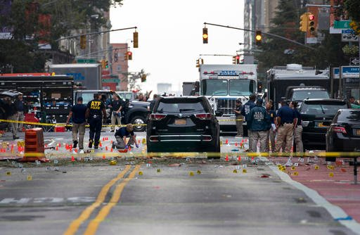 Crime scene investigators work at the scene of an explosion on West 23rd street in Manhattan's Chelsea neighborhood, in New York, Sunday, Sept. 18, 2016, after an incident that injured passers-by Saturday night. (AP Photo/Craig Ruttle)