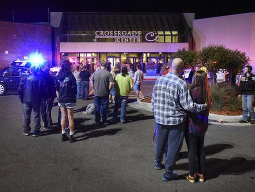 People stand near the entrance on the north side of Crossroads Center mall between Macy's and Target as officials investigate a reported multiple stabbing incident, Saturday, Sept. 17, 2016, in St. Cloud, Minn. (Dave Schwarz/St. Cloud Times via AP)