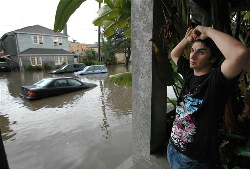 Chris Rogers takes shelter on a neighbors porch after leaving his home when water started to rush in following a severe downpour in Long Beach, Calif., Tuesday, Jan. 19, 2010.