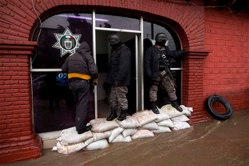 Tijuana police officers stand guard on sand bags placed to prevent the police station from flooding in Tijuana, Mexico, Thursday, Jan. 21, 2010.