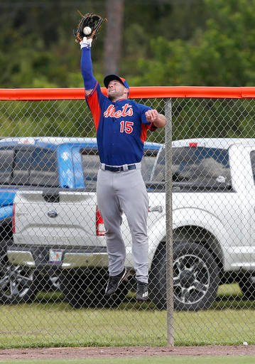 Tim Tebow catches a ball at the fence during a drill at the New York Mets' complex, Monday, Sept. 19, 2016, in Port St. Lucie, Fla.