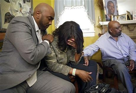 Attorney Damario Solomon-Simmons, left, comforts Tiffany Crutcher, twin sister of Terence Crutcher who was shot and killed by Tulsa Police Friday night Sept. 16, 2016. At right is Rev. Joey Crutcher, her and Terence's father. (Mike Simons/Tulsa World via