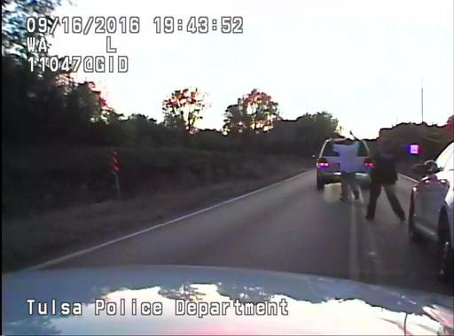 In this image made from a Friday, Sept. 16, 2016 police video, Terence Crutcher, left, is pursued by police officers as he walks to an SUV in Tulsa, Okla. Crutcher was fatally shot Friday after authorities say an officer stopped to investigate the stalled