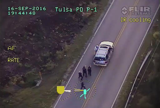 In this image made from a Friday, Sept. 16, 2016 police video, Terence Crutcher, top, is pursued by police officers as he walk to an SUV in Tulsa, Okla. Crutcher was taken to the hospital where he was pronounced dead after he was shot by the officer aroun