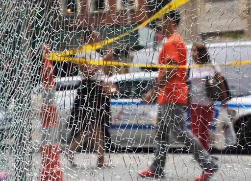 New Yorkers pass a shattered storefront window on W. 23rd St. in Manhattan, Tuesday, Sept. 20, 2016, in New York. The window was hit by shrapnel from the terrorist bomb that exploded across the street Saturday evening. An Afghan immigrant wanted in the bo