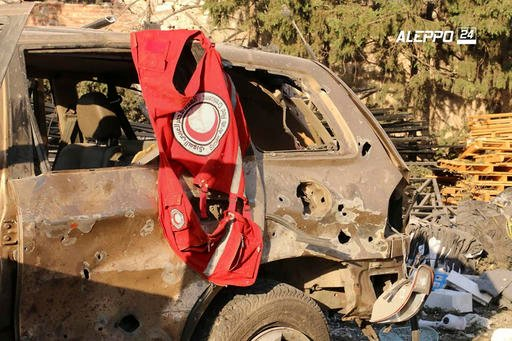 This image provided by the Syrian anti-government group Aleppo 24 news, shows a vest of the Syrian Arab Red Crescent hanging on a damaged vehicle, in Aleppo, Syria, Tuesday, Sept. 20, 2016. A U.N. humanitarian aid convoy in Syria was hit by airstrikes Mon