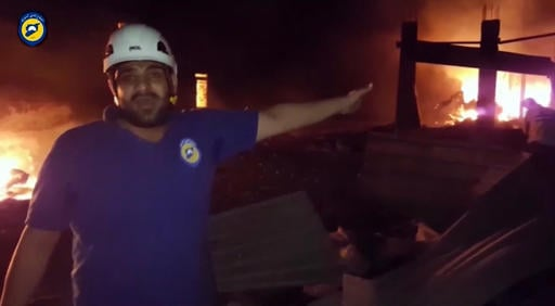 In this grab taken from video provided by the Syrian Civil Defence White Helmets, a member of the team describes the damage after an airstrike, in Aleppo, Syria, Monday, Sept. 19, 2016. At least 12 aid workers and truck drivers were reported killed in Syr