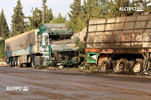 This image provided by the Syrian anti-government group Aleppo 24 news, shows damaged trucks carrying aid, in Aleppo, Syria, Tuesday, Sept. 20, 2016. A U.N. humanitarian aid convoy in Syria was hit by airstrikes Monday as the Syrian military declared that