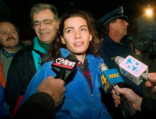 FILE - In this Feb. 9, 1994 file photo United States olympic skater Nancy Kerrigan speaks with members of the media as her father Daniel Kerrigan, left, looks on at Logan International Airport, in Boston