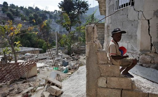 Jean Louis Moint waits for his parents near the remains of his home after it was destroyed during the Jan. 12 earthquake in Port-au-Prince, Wednesday, Jan. 27, 2010. (AP Photo/Gregory Bull)